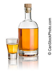 Bottle and shot glass filled with amber liquid