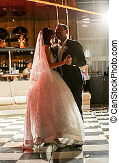 just married couple dancing at dark hall a beam of light -...