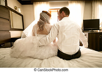 bride and groom sitting on bed and hugging - Photo from back...