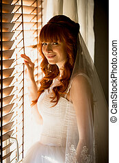 young bride opening jalousie at sunny day