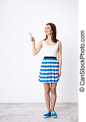 Full length portrait of a smiling beautiful woman pointing...