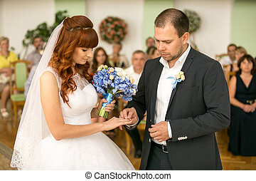 handsome groom putting wedding ring on brides hand at...