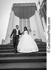 Monochrome photo of beautiful just married couple walking...