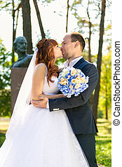 portrait of just married couple kissing in park at sunny day