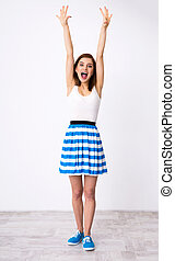 Full length portrait of a funny woman with raised hands up