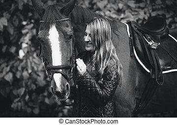 black and white portrait of smiling woman walking with horse...