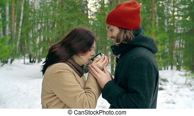 Warm Senses - Young couple cuddling outdoors and drinking...