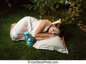 young woman in nightgown sleeping on grass at garden at...