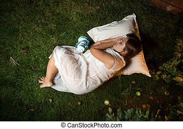 brunette woman sleeping at night garden on pillow -...