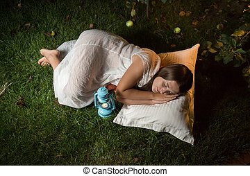 cute woman sleeping in garden at night - Outdoor shot of...
