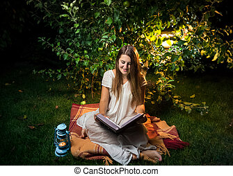 smiling woman sitting at night in garden and reading big old...