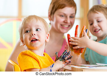 Cute woman playing and painting with children in playschool...