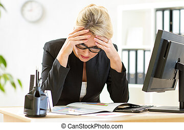 thoughtful business woman analyzing reports in office