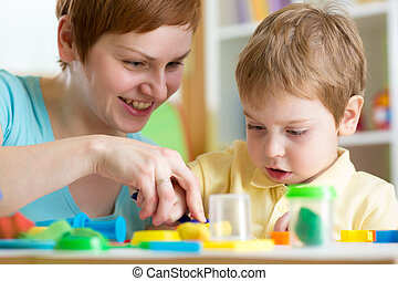 child boy and mother playing colorful clay toy - smiling...