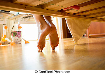 Closeup shot of female feet under bed at morning