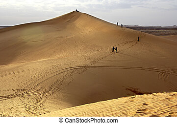 Tourists climbing a sand dune in the Great Libyan Desert,...