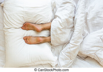 feet lying on soft white pillow at bed - Closeup view of...