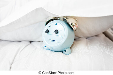 conceptual photo of alarm clock under pillow on bed -...