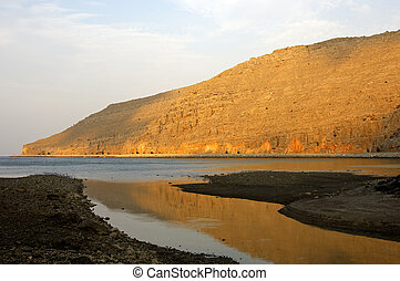 Morning light on the bare rocks of fjord on the Musandam...