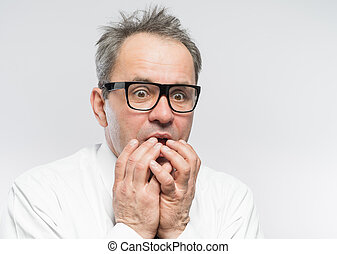 Closeup portrait of a nerdy guy with glasses biting his...