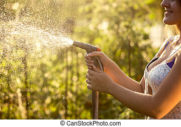 Closeup photo of woman watering garden with hosepipe at hot...