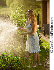 brunette woman in dress working at backyard with hosepipe -...
