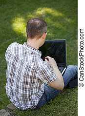 working with laptop outdoor - man with laptop working in a...