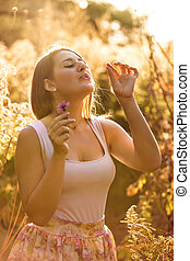 portrait of beautiful woman blowing petal from flower at...