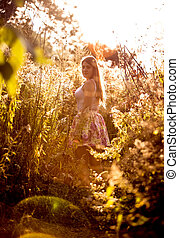 landscape of meadow at sunny day with woman walking on path...