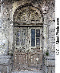 Old weathered gray wooden vintage door with decoration