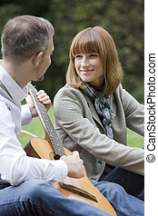 romantic dating, man plays guitar and woman hears his song