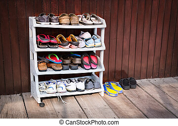 Colorful Shoes on a Plastic Shoe Rack, Outside a House - A...