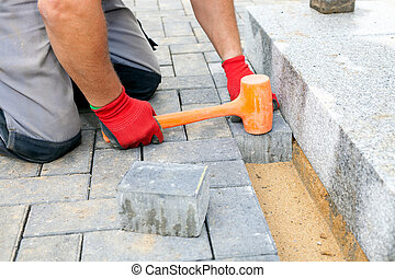 Creating a pavement Close up - Bricklayer places concrete...