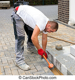 A worker creates a terrace of concrete paving stones. -...
