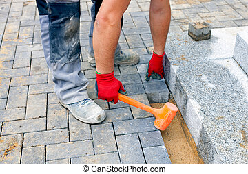 Construction worker putting concrete paving stones - Close...