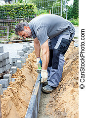 Construction worker place border stones. - Paver separate a...