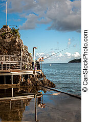 fisherman standing with rod on wooden pier at rocky shore