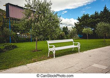 white bench in park with trees and lawn