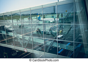 airliner reflecting in glass wall of modern airport terminal...