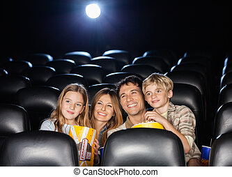 Happy Family Watching Film In Theater - Happy family of four...