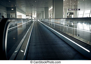 long horizontal escalator at international airport terminal...