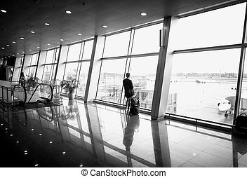 Monochrome photo of woman standing in front of big window at...