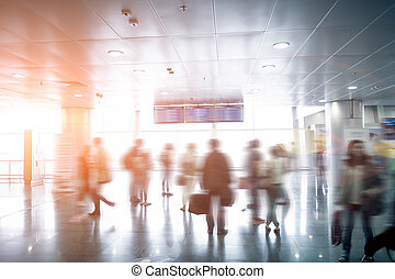 blurred passengers looking at airport schedule at sunny day...
