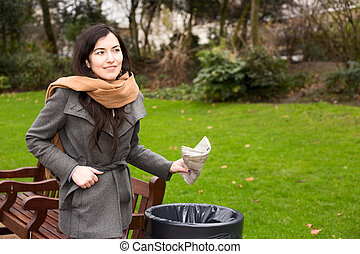 young woman throwing rubbish in a bin