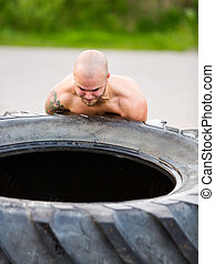 Male Athlete Lifting Truck Tire - Dedicated young male...