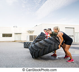 Athletes Flipping Tires - Young male and female athletes...