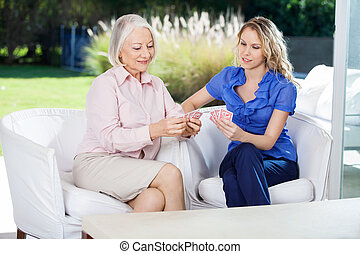 Card game with Senior and Mid adult woman - Care aid playing...