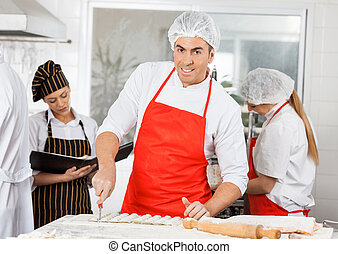 Smiling Chef Preparing Ravioli Pasta With Colleagues In...