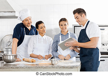 Chefs Checking Recipe On Tablet Computer In Kitchen - Male...