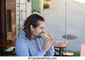 young guy with long hair eats big sandwich